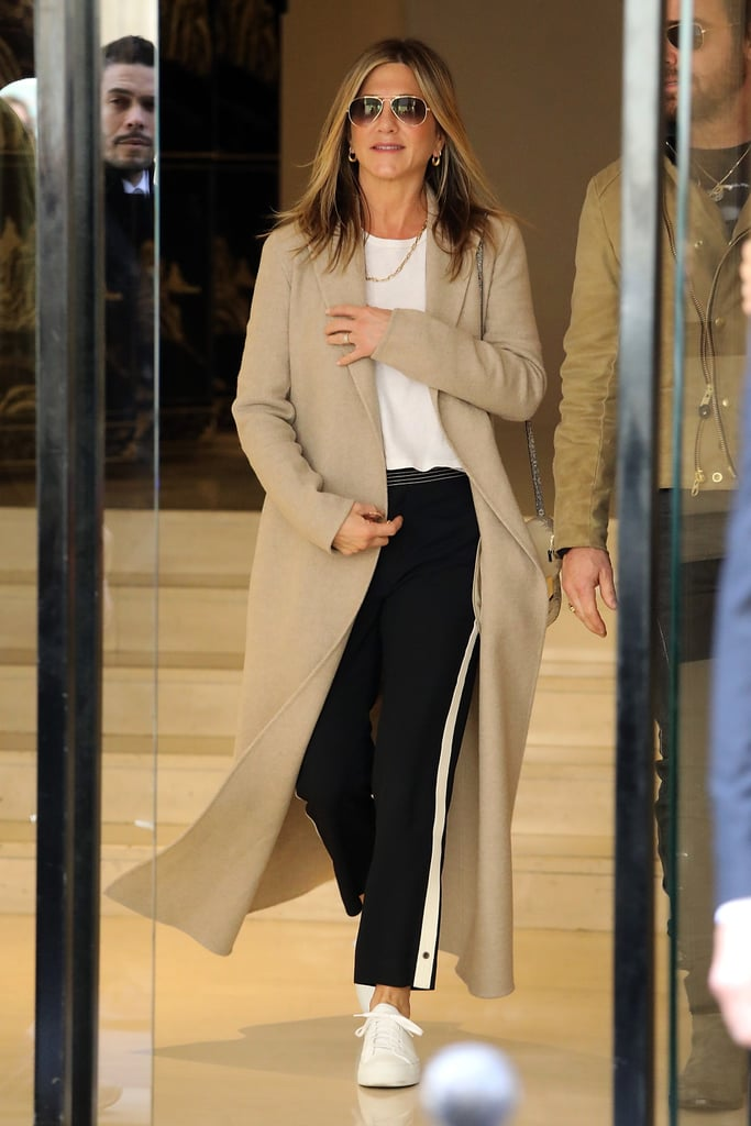 In April 2017, Jennifer wore a pair of black, side-striped pants with a plain white tee and white sneakers. She elevated her look by throwing on a camel-colored coat and gold-trimmed aviators.