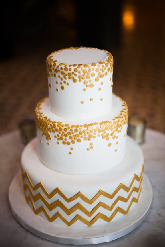 An all-white cake is given a graphic touch with a chevron base and metallic circles.