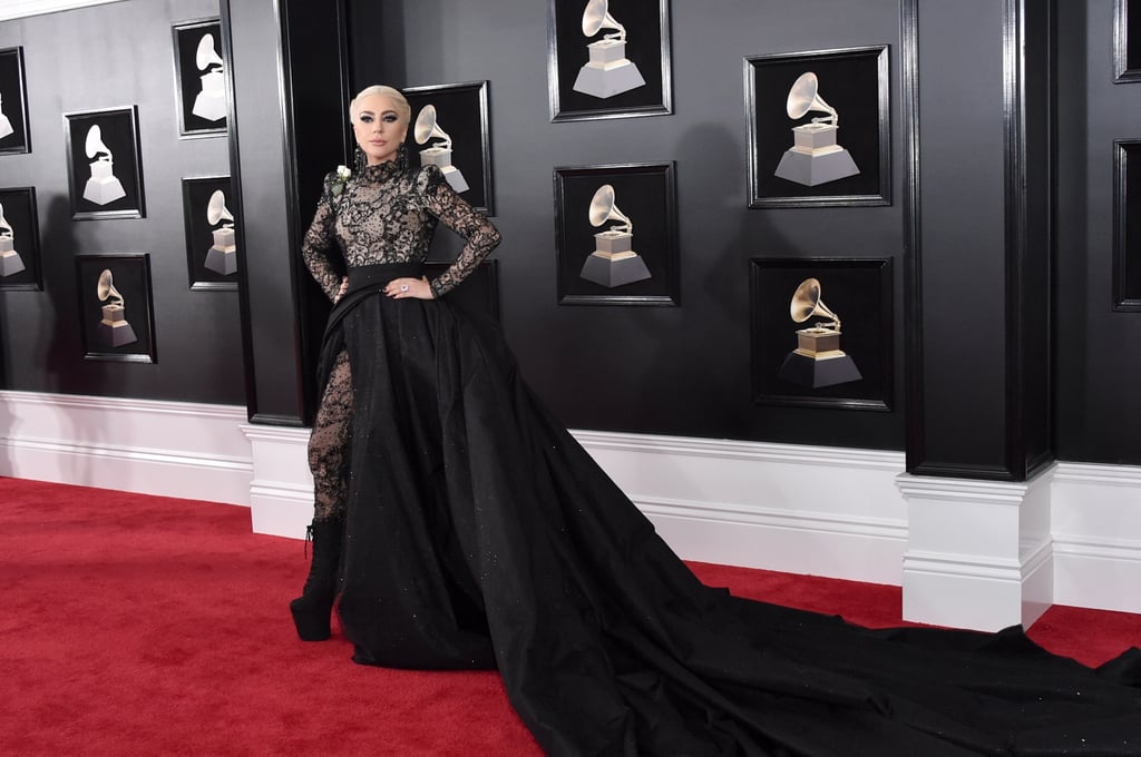 Lady Gaga was just one of the many stars who stunned at the 2018 Grammy Awards on Sunday. The songstress walked the red carpet wearing a black dress with a dramatic skirt by Armani Privé. Her Gothic-inspired gown featured a sheer bodice with beaded embellishments and lace accents. It wasn't until she moved to the side that we realized her gown had a thigh-high slit, and the sheer bodice was actually a full bodysuit, which Gaga fully revealed once she was inside at the award ceremony, ditching her skirt entirely. Lady Gaga finished her look with platform boots, an intricate, corset-inspired braid and Lorraine Schwartz jewels. Keep reading to see her stunning style from every angle — and just how revealing it got as the evening progressed.