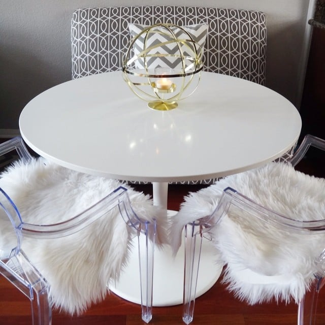 The finds: the patterned bench, ghost chairs, and sheepskin-style furs seen in this chic dining nook.