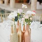 Spray-paint empty bottles in metallic tones for vases.