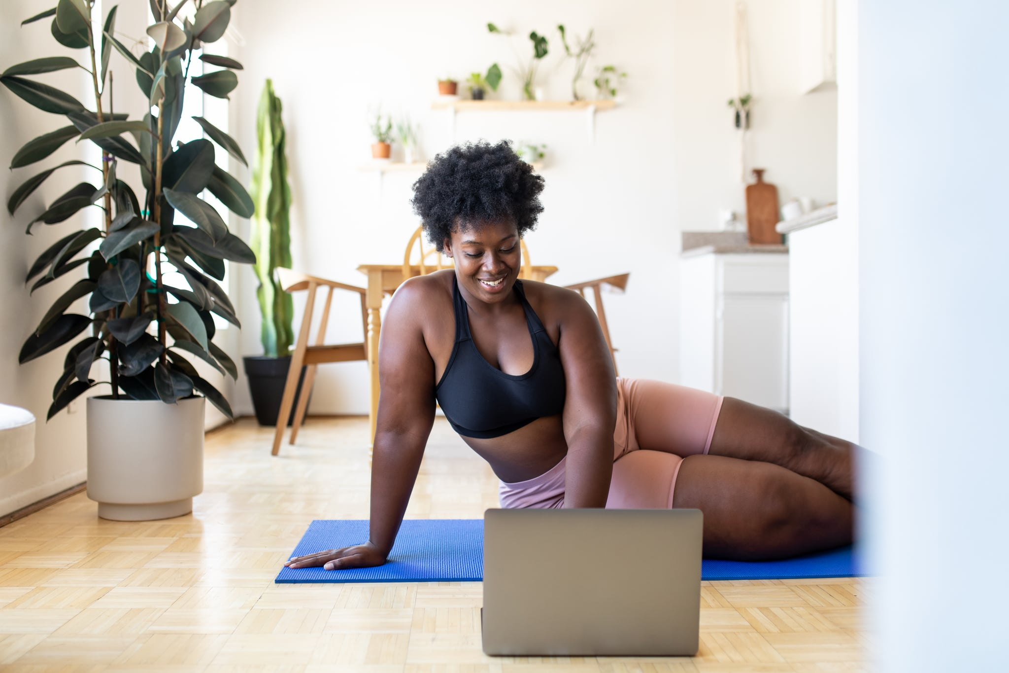 Woman in sportswear using laptop at home. Young woman searching for online exercise tutorials on a laptop at home.
