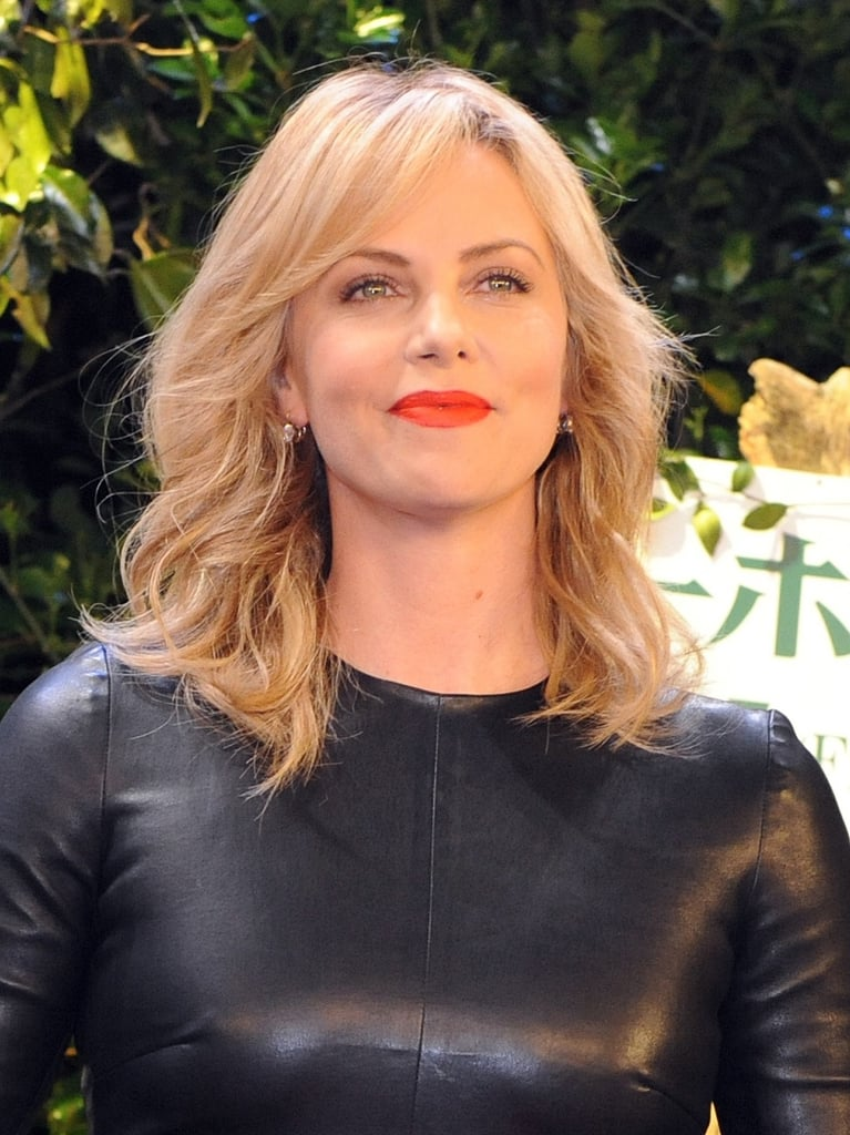 Charlize stunned in loose waves and a bold red lip in Tokyo.