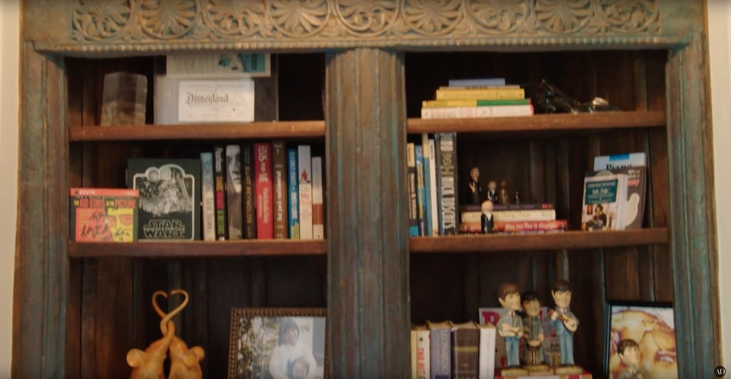 Right outside their room, there's a wooden bookshelf filled with trinkets, photos, and books.