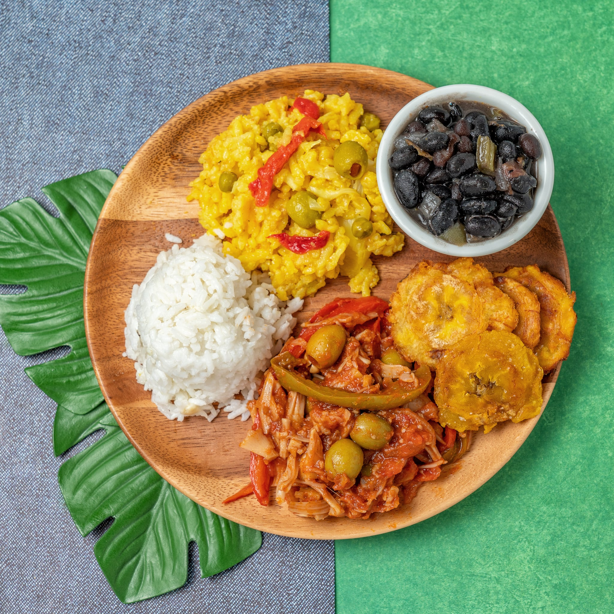 A top view of a Cuban food plate that includes yellow rice (arroz con pollo), ropa vieja, fried plantain, white rice and black beans. Shown on a wooden platter with tropical background.