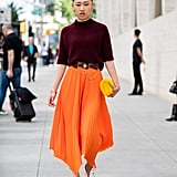If you're a little wary of bright color, consider trying out a midi skirt that's styled with a deeper and more neutral tone on top.