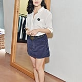 Wearing a classic white blouse and blue skirt at an event in 2018.