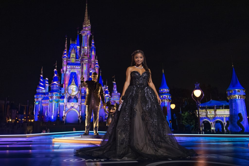 """Halle Bailey kicked off October in style and all black, fittingly. The singer and star of the upcoming live-action remake of The Little Mermaid recently performed """"Can You Feel the Love Tonight,"""" from The Lion King, as part of an ABC special celebrating the 50th anniversary of Walt Disney World.  For the concert, which took place at Magic Kingdom, Halle wore a dramatic black Elie Saab gown with sparkly appliqués and a sweetheart neckline. Styled by Nikki Cortez, the look was paired with diamond jewelry by Nadine Aysoy. Ahead, take a closer look at the striking outfit, which coincides quite nicely with the start of the Halloween season. (Yes, it's a whole season.)       Related:                                                                                                           Chloe and Halle Bailey's Sheer Designer Gowns Are Proof That All Good Things Come in Pairs"""