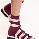A trainer that extends into a striped sock.