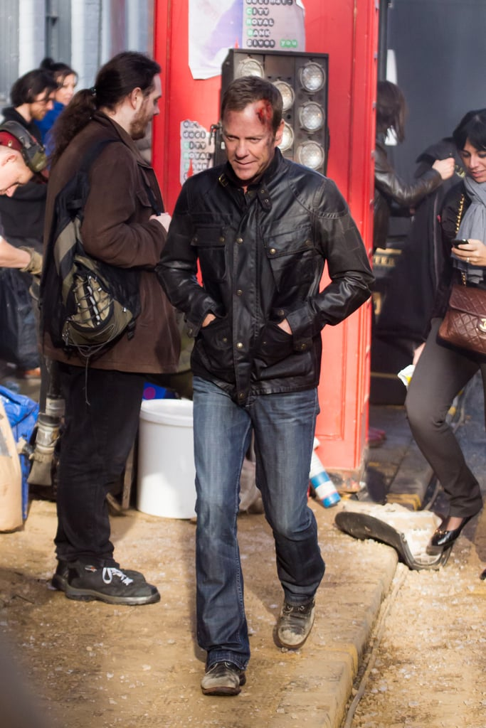 "Kiefer Sutherland made his first appearance on the London set of 24: Live Another Day! He got into character as everyone's favorite small-screen hero, Jack Bauer, on Wednesday, filming an action scene with blood on his face and a gun in his hand. There was even a massive car explosion in the street and an apparently injured accomplice — stuff 24 dreams are made of.  It's been almost four long years since the hit series was canceled and a whole nine months since rumors of a TV reboot got started (not to be confused by the chatter about a possible movie). Kiefer and executive producer Manny Coto helped clear up the confusion about 24: Live Another Day at a Winter TCA panel last week, when they shared that the special series will be 12 episodes long and still take place over the course of one day with some skips in time. Fans should also prepare for the fact that Jack and Chloe will be ""pitted against each other"" this time around. Scroll for more images of Jack in action before the big premiere on May 5!"
