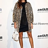 Giovanna Battaglia arrived at amfAR in a black sheath topped with a statement-making sequined coat and finished with ankle-strap Valentino heels.