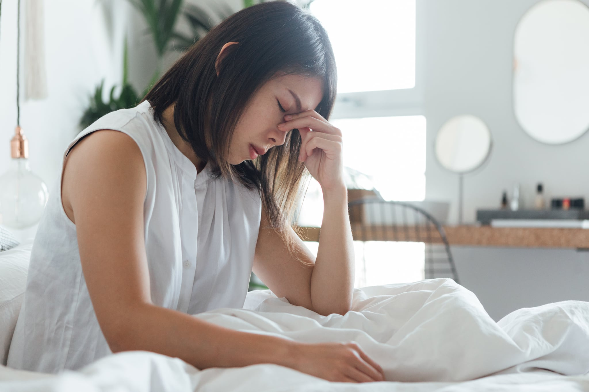 Young woman touching bridge of nose to relieve headache while resting in bed.