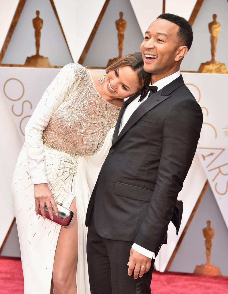 """We can always count on Chrissy Teigen and John Legend to pack on the PDA, and their latest outing was no different. On Sunday, the pair stepped out at the Oscars in LA looking like an absolute dream. Not only did they play up their sweet chemistry, hugging and laughing while posing for pictures, but during their red carpet interview with Ryan Seacrest, John told Chrissy, """"You look like a goddess. I'm very pleased."""" Consider our hearts destroyed."""