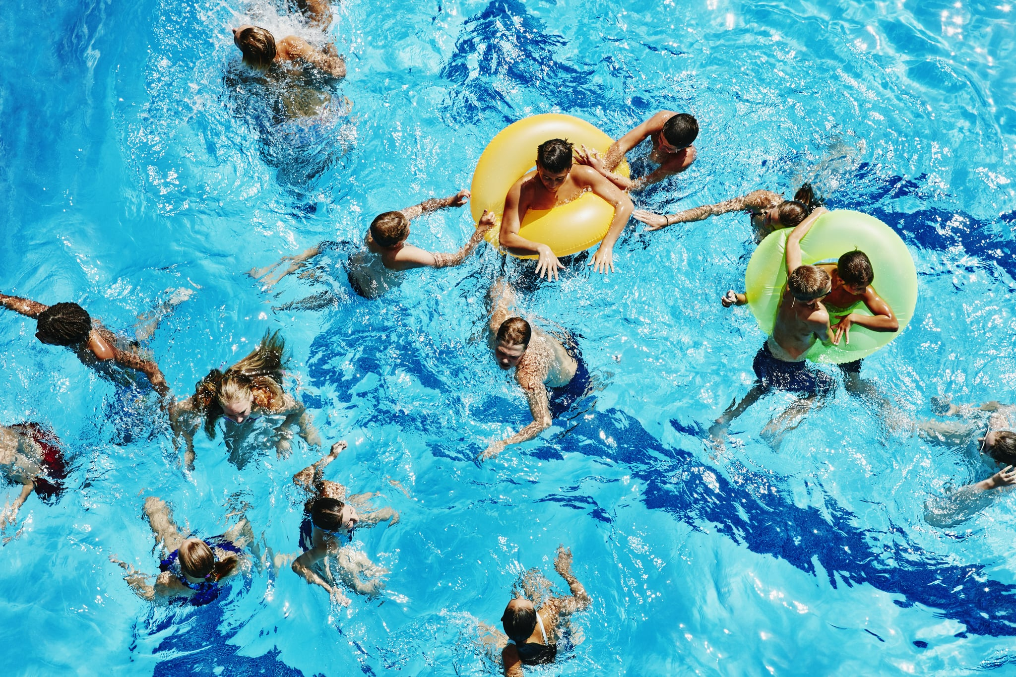 Group of kids playing together in outdoor pool overhead view