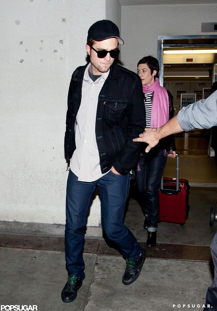 Robert Pattinson got off of a plane at LAX wearing a black jacket and jeans.