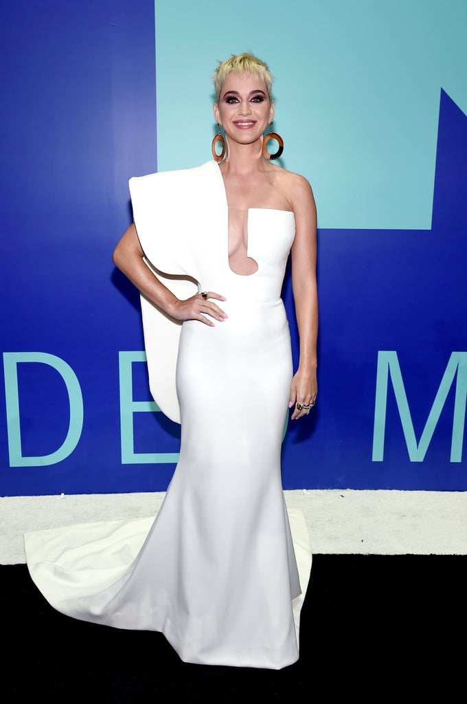 If Taylor Swift was on Katy Perry's mind, she showed no signs of it at the 2017 MTV VMAs. The star first walked the blue carpet in a Stéphane Rolland gown, smiling as she posed for the cameras. The one-shoulder dress featured a cutout in the middle and clean, sculptural lines at the hem. This sexy dress, however, was just the beginning of several outfit changes for the host. Katy wore everything from a space suit to a silver, body-hugging gown. The singer had nothing to worry about (at least in the style department) because her looks set her up for best dressed of the night. Read on to see all her outfits.