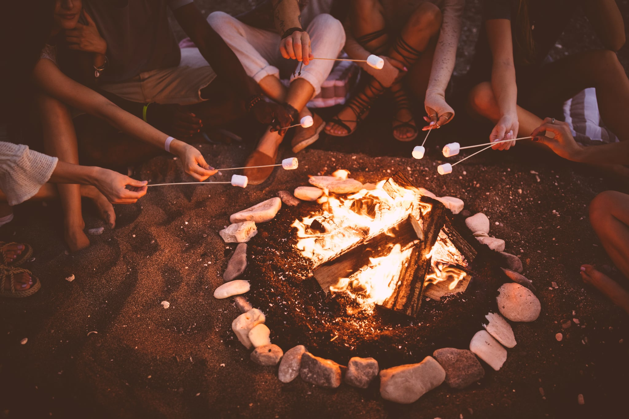 Close-up of young multi-ethnic hipster friends' hands roasting marshmallows over bonfire on camping trip