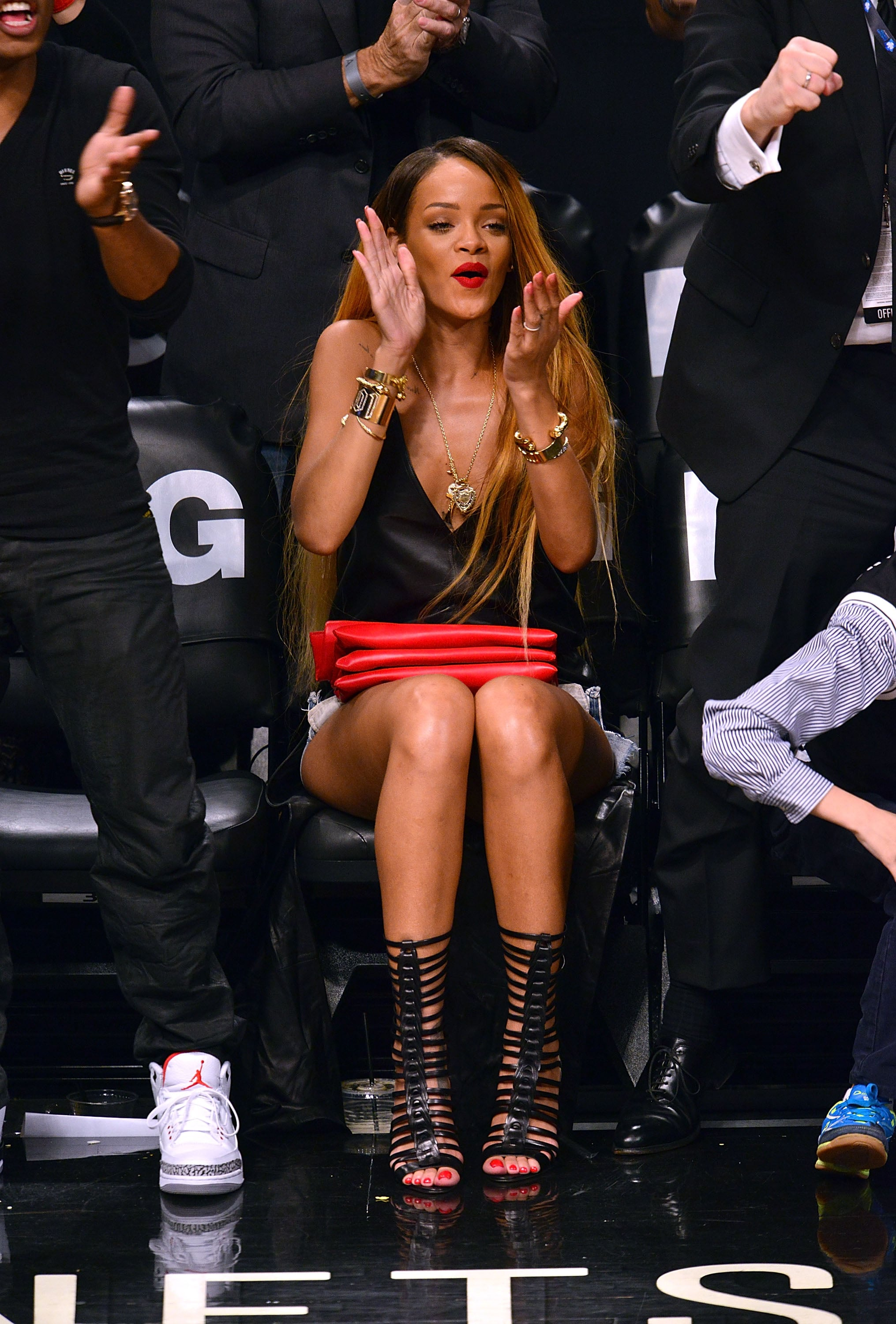 Rihanna sat courtside at a Brooklyn Nets playoff game in April looking risqué in a black leather tank and caged sandal boots by Brian Atwood. For accessories, the singer chose a bright red clutch and a bevy of gold jewels.