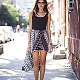 A high-low hemline adds intrigue to a basic tank — further the effect with cool-girl ankle boots.