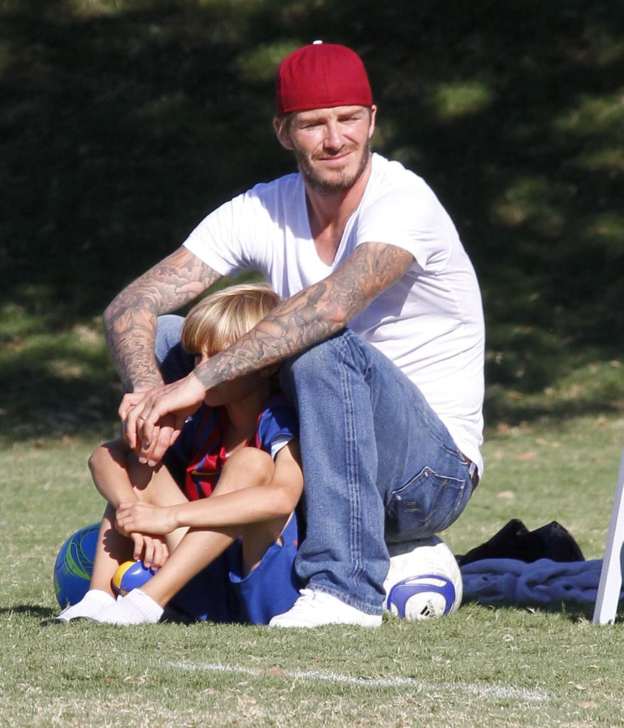Romeo Beckham sat on the sidelines with David Beckham.