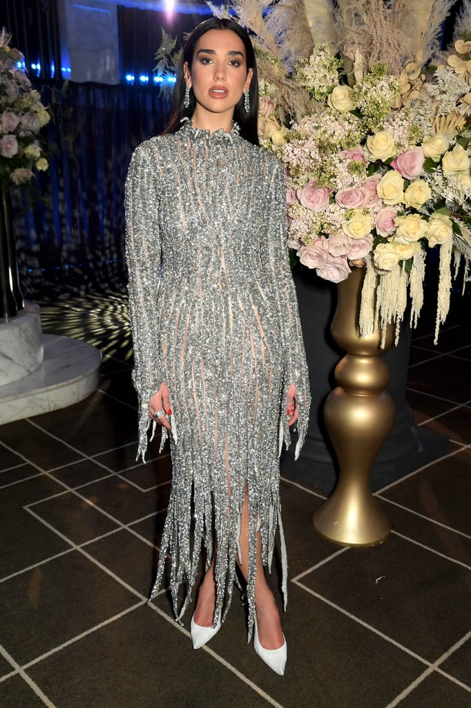 """Diamonds were the standout star on both of Dua Lipa's performance gowns at the Oscars preparty benefit hosted by the Elton John AIDS Foundation. The Future Nostalgia singer started her string of solo performances in a black gown and later changed into a sparkling outfit to perform duets of """"Bennie and the Jets"""" and """"Love Again"""" with Elton John.  Dua Lipa is no stranger to a very sexy red carpet moment, particularly if it's sparkling. Her glimmering butterfly Grammys dresses are already some of the defining red carpet outfits of 2021. But while Lipa usually goes for '90s-inspired dresses or sexy, sheer looks, her Oscars preparty gowns were expectedly formfitting but impressively elegant.  Dua Lipa's first look was a black velvet high-neck and long-sleeved Balenciaga gown that featured a billowing peplum hem and jewelry by Bulgari. Her second gown was also Balenciaga — a high-neck, long-sleeved design featuring head-to-toe silver crystals with sheer, mesh paneling, shredded sleeves, and a fringed hemline that looked inspired by Morticia Addams's gothic gown in the 1960s series The Addams Family. Lipa's stylist Lorenzo Posocco completed the singer's look with white Balenciaga pointed-toe heels, Chopard earrings, and a Fabergé ring. Keep reading for a closer look at Dua Lipa's gorgeous Oscars preparty gowns."""