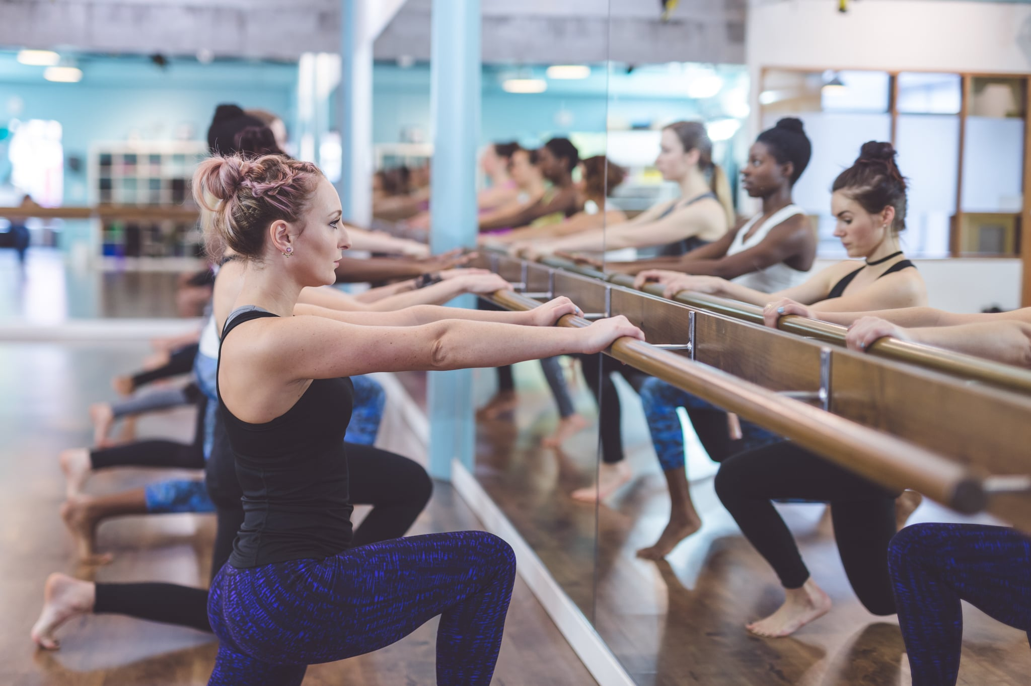 A multiethnic group of young women do a barre workout together at a modern gym. They are facing the mirror on the wall, gripping the barre, and squatting as they go through their lunge repetitions.
