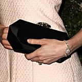 Her jewel-fastened black clutch and Bouton Camelia bracelet were both by Chanel too.
