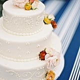 Ranunculus, roses, and dahlias pop against the dotted-lace piping of this wedding cake.