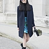 With trainers and a chic overcoat.