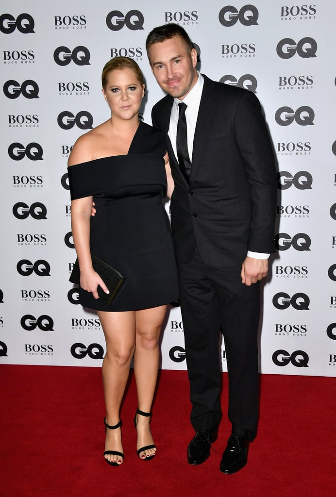 Amy Schumer had the support of her boyfriend, Ben Hanisch, at the GQ Men of the Year Awards in London on Tuesday. At the event, the comedian linked up with pal Florence Welch and was honored with the woman of the year award for her role in Trainwreck as well as the release of her new book, The Girl With the Lower Back Tattoo.   While Amy and Ben have been dating since December 2015 and attended award shows together, the GQ event marked the couple's first joint red carpet appearance and Amy's first public outing since her controversial interview with Lena Dunham. Lena grabbed headlines last week after disparaging comments about NFL star Odell Beckham Jr. were published in her Lenny newsletter. To make matters worse, Amy stirred up more controversy over the weekend when she tweeted and deleted a racist comment about men of color. The actress has yet to publicly address the incident.