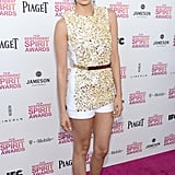 Nina Dobrev shined in a gold-embellished top, white shorts, and slick gold belt — all by Michael Kors. She kept her hair up in a simple ponytail, then accesorized with nude Jimmy Choo sandals and an H. Stern ring.