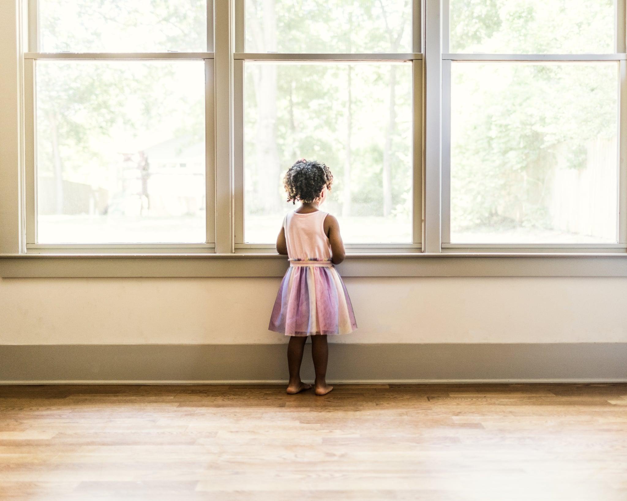 Portrait of preschool age girl looking out window