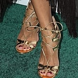 Street style star Olivia Palermo sported metallic gold lace-up sandals for an event this Fall.
