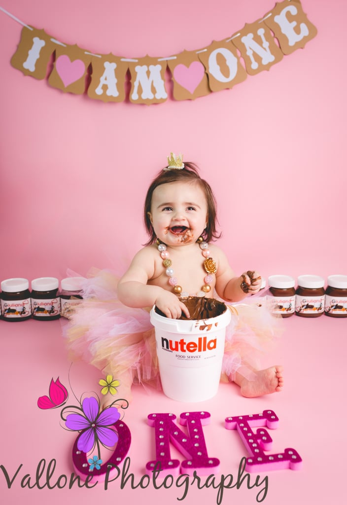 "Although cake smashes to celebrate a little one's first birthday aren't anything new, the idea of smashing something other than cake (like tacos, for instance) is still pretty fresh. For Giuliana's first birthday, her parents suggested a Nutella smash to their photographer, Benedetta Vallone, and the rest is history. ""I couldn't have been more excited,"" Vallone told POPSUGAR. ""At first Giuliana wasn't into her bucket of Nutella, but slowly and surely she dived into the tasty treat."" Because what human wouldn't?      Related:                                                                                                           Thanksgiving Food and 10 Other Genius Ideas For a First Birthday Smash Sans Cake"