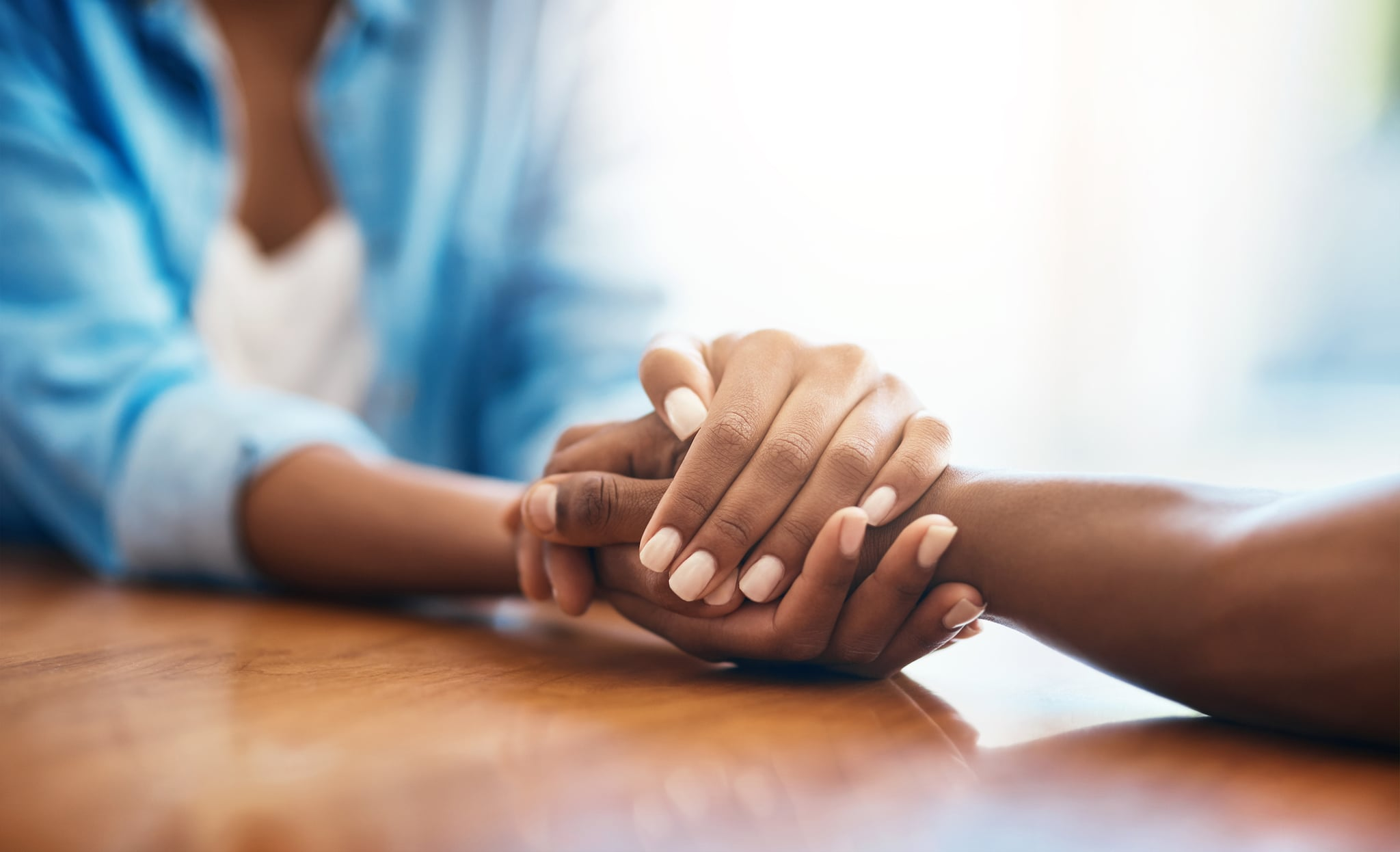 Closeup shot of two unrecognisable people holding hands in comfort at home