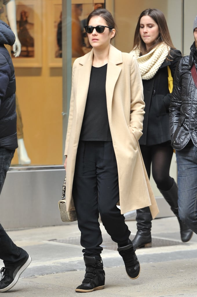 Marion Cotillard looked Parisian chic wearing a luxe camel coat with black Isabel Marant sneakers and matching accompaniments in NYC.