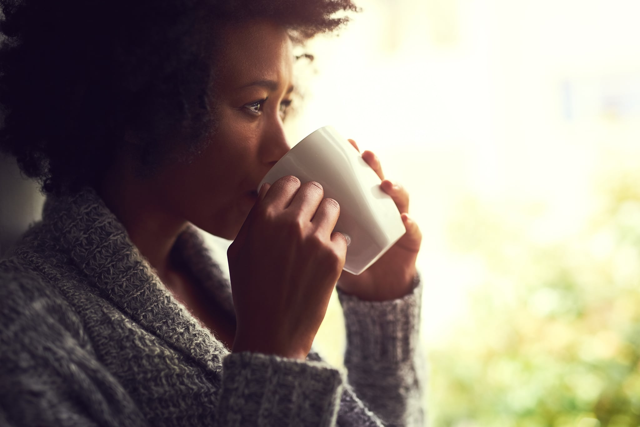 Shot of a relaxed young woman enjoying a cup of coffee while sitting by a window at home