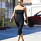 Chrissy kept it casual in a strapless black dress that showed off her barely there bump. She paired the  skintight piece with golden Giuseppe Zanotti sandals and Victoria Beckham aviator sunglasses.