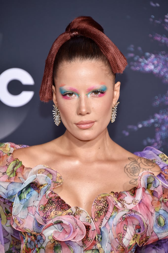 """All eyes were on Halsey's eyes at the American Music Awards on Sunday night. The """"Graveyard"""" singer didn't hold back with her colorful makeup on Nov. 24 and certainly brought the watercolor trend to new heights.  Halsey matched her romantic floral gown with an array of colorful shades on her lids and delicate rhinestones by the bridge of her nose. She elevated her makeup even more by extending the hues past her eyebrows. Here's a lesson straight from Halsey's book: why be subtle when you were born to stand out? Ahead, get a closer look at her full beauty look, then get the details on her floral dress."""