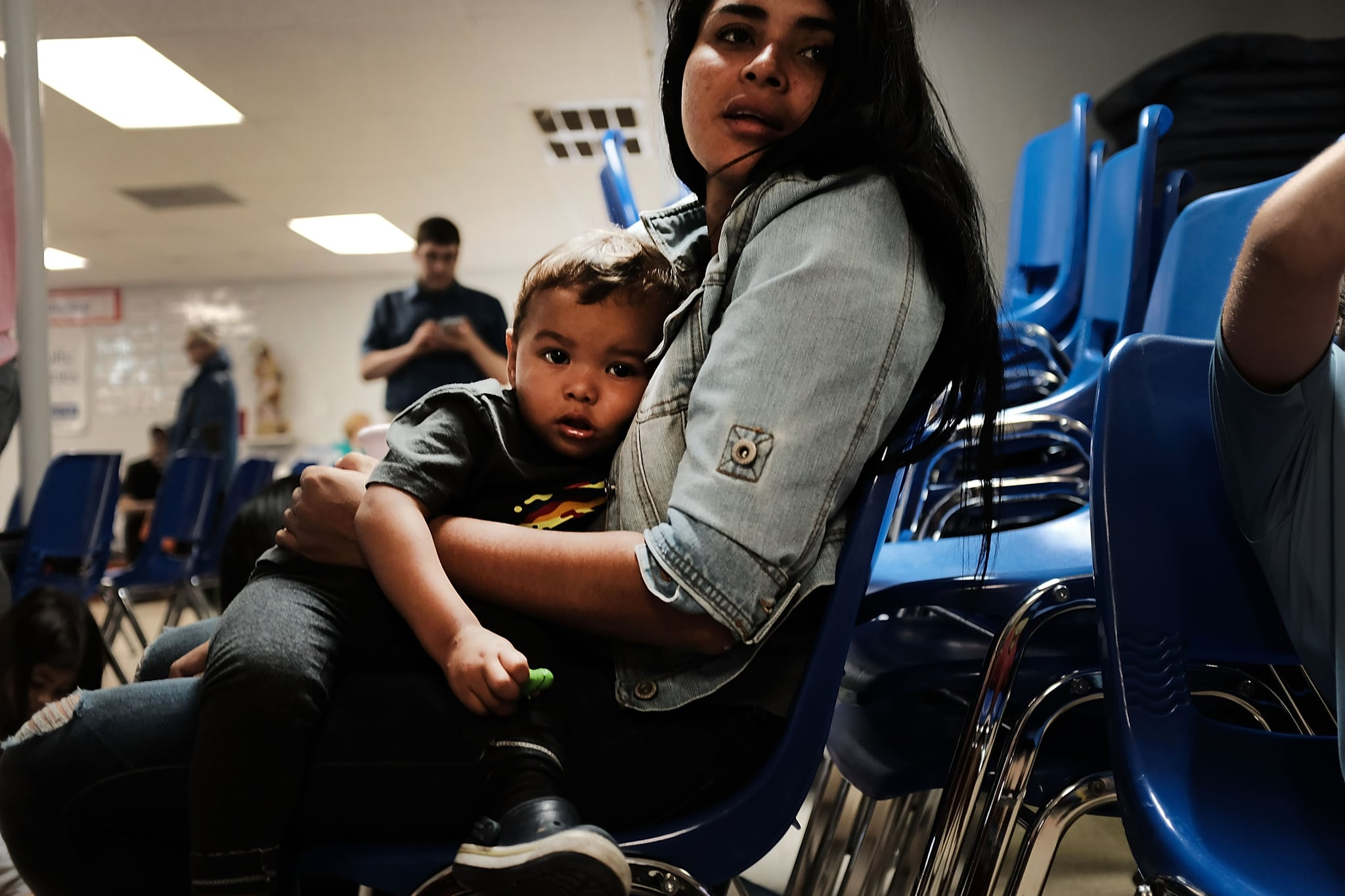 MCALLEN, TX - JUNE 21: A woman who idendtified herself as Jennifer sits with her son Jaydan at the Catholic Charities Humanitarian Respite Centre after recently crossing the U.S., Mexico border on June 21, 2018 in McAllen, Texas. Once families and individuals are released from Customs and Border Protection to continue their legal process, they are brought to the centre to rest, clean up, enjoy a meal and get guidance to their next destination. Before Trump signed an executive order yesterday that the administration says halts the practice of separating families seeking asylum, more than 2,300 immigrant children had been separated from their parents in the  zero-tolerance policy for border crossers. (Photo by Spencer Platt/Getty Images)