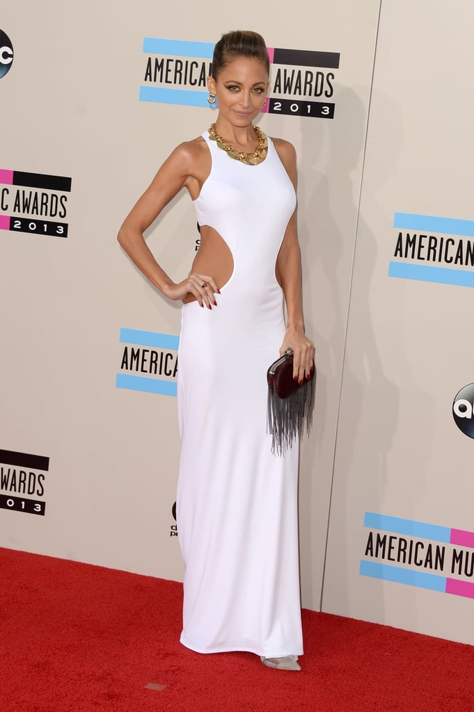 Nicole Richie never gets it wrong, and her latest look at the American Music Awards is proof! Strategic side cut-outs sexed up a fitted white gown, while her fringed clutch finished the look.