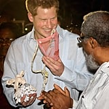 Prince Harry smiled as he tried on a mask during a block party in Belize.