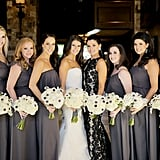 There were pops of gray in the bridal party's bouquets to match the seven bridesmaids' dresses, while the maid of honor stood out in a patterned black and beige number.