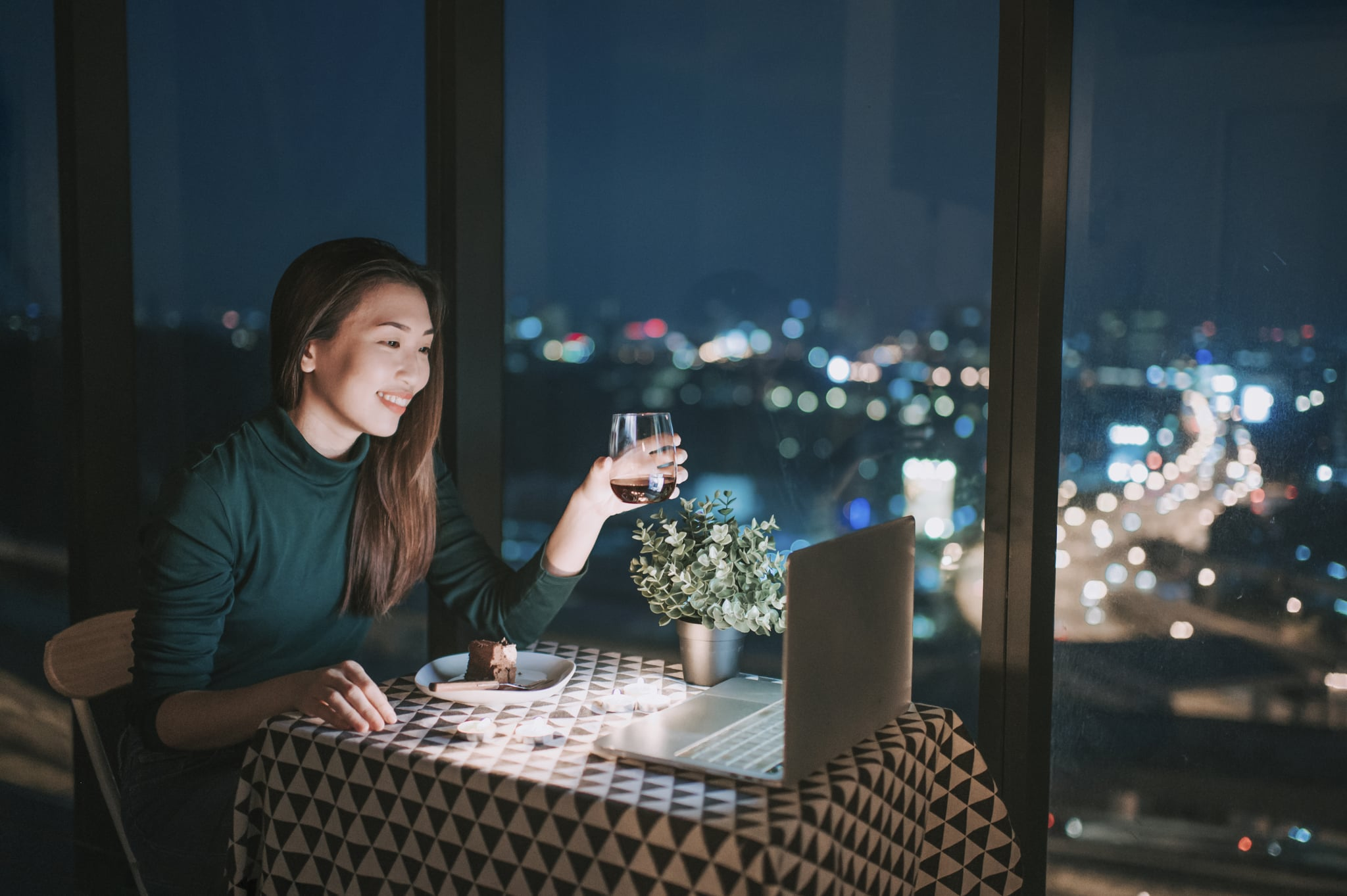 an asian chinese beautiful young lady having dessert in her apartment during magic hour, dusk and talking to her boyfriend thru internet using her laptop