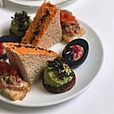 "There's obviously a Maleficent-inspired snack on the villain-centric menu. It's the green one with ""horns"": toasted pumpernickel bread with an edamame-avocado smash, sweet chili, bacon, and fried ruby red, a type of microgreen."