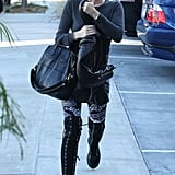 Miley Cyrus carried a black purse and jacket.
