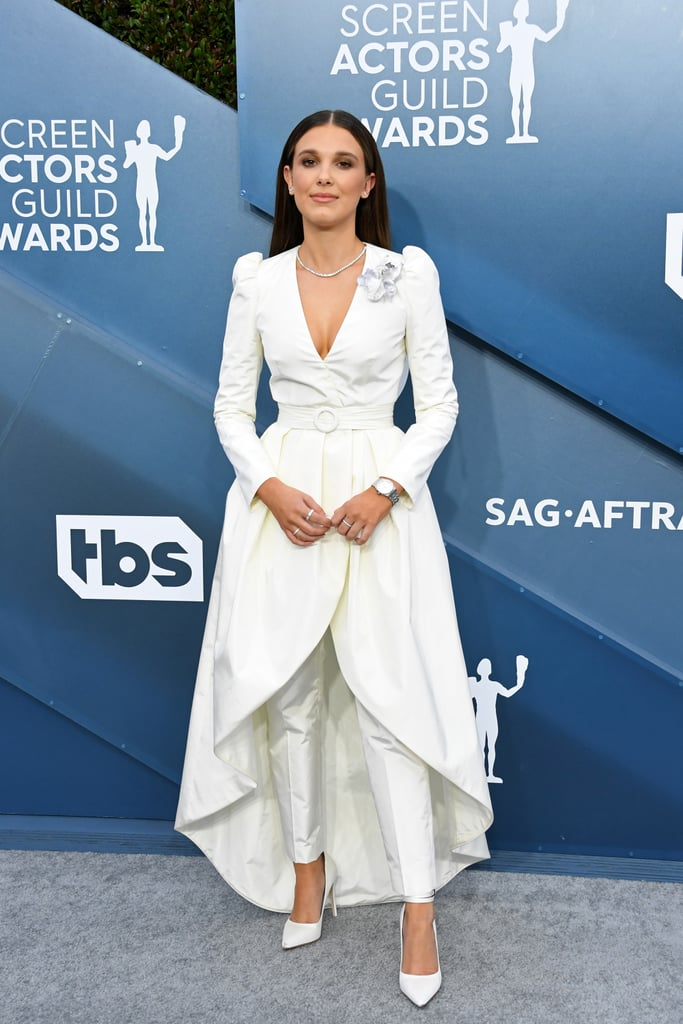 Millie Bobby Brown redefined the skirt suit at the 2020 SAG Awards. The Stranger Things actress attended the star-studded award show on Jan. 19 wearing a custom-made Louis Vuitton outfit consisting of tailored trousers and a high-low, belted dress jacket featuring a modern boutonniere.  Styled by Thomas Carter Phillips, the outfit was complemented by satin, pointed-toe pumps also by Louis Vuitton, and a casual amount of Cartier jewelry, including a diamond necklace, earrings, and several rings. Get a closer look at Millie's classic and crisp outfit ahead, and then check out photos of Millie hanging with her Stranger Things costars on the red carpet.