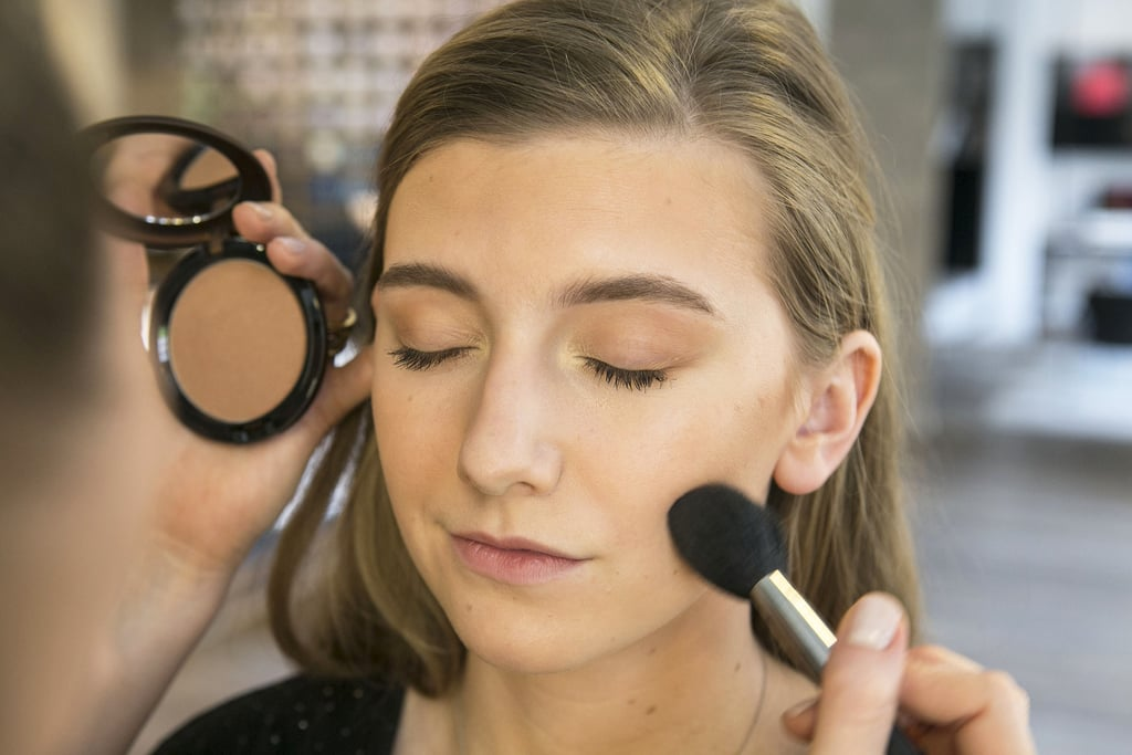 "Once your foundation is blended (even on the neck), grab your favorite bronzer — Bettelli likes Pro Longwear Bronzer ($30) — and use a fluffy powder brush to apply it along your hairline, cheekbones, neck, and jaw. ""I like to sweep the bronzer across the face in a W shape to subtly contour the nose and cheeks."""