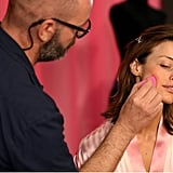 Makeup artist Dick Page dabs a BeautyBlender on Flavia Lucini's cheek.