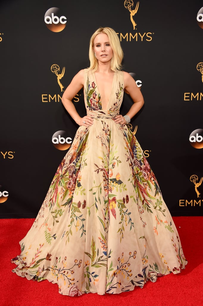 Summer is ending in several days, but you wouldn't know that from looking at Kristen Bell's dress. After teasing her look on Instagram, she graced the Emmys red carpet in a Zuhair Murad floral gown. The colorful flowers and leaves contrasted against the beige dress gave the outfit a romantic, almost fairy-tale-like feel, while the plunging neckline offered just the right amount of sexiness. We're definitely feeling all the Summer vibes from her look, and you will too when you scroll ahead to the photos here.